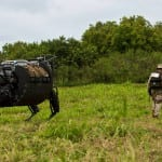 Kaneohe Bay, Hawaii - The Legged Squad Support System (LS3) on patrol with a Marine during the Advanced Warfighting Experiment (AWE), part of RIMPAC 2014. Photo courtesy  Marine Corps Warfighting Laboratory.