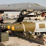 Airmen load a 2,000 pound GBU-31 Joint Direct Attack Munition onto a B-1B Lancer aircraft.
