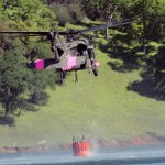 A UH-60 Black Hawk helicopter of the California Army National Guard hovers above Lake Pardee in Ione, California, collecting water in a bucket, April 14, 2018, during wildland firefighting training, a cooperative mission between Cal Guard and the California Department of Forestry and Fire Protection (CAL FIRE). (U.S. Army National Guard photo by Staff Sgt. Eddie Siguenza)