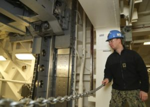 Electrician's Mate 3rd Class Mitchell McBride assigned to USS Gerald R. Ford's (CVN 78) weapons department, observes Advanced Weapons Elevator (AWE) upper stage no. 3. AWE no. 3 was accepted by the ship on February 14, the second elevator accepted on the ship. Ford is undergoing a post-shakedown availability at Huntington Ingalls Industries-Newport News Shipbuilding. (Photo: U.S. Navy)